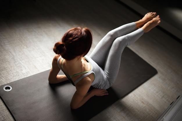 明るい窓の近くのジムに座ってヨガストレッチ運動をしている若いスポーティな女性。