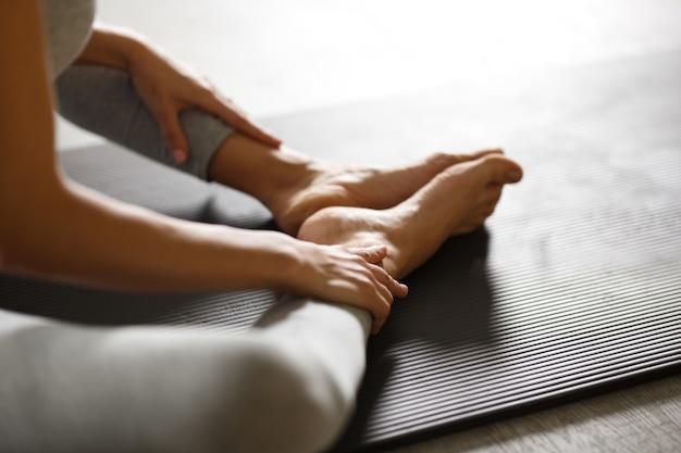 Молодая спортивная женщина делает упражнения на растяжку йоги, сидя в тренажерном зале возле ярких окон.