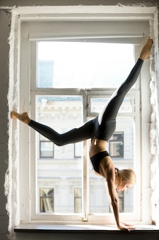 Young sporty woman in downward facing tree pose, window sill