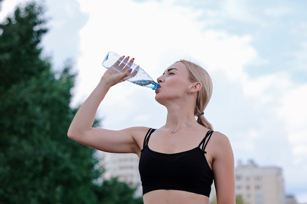 Young sporty woman drinking still water from a bottle.