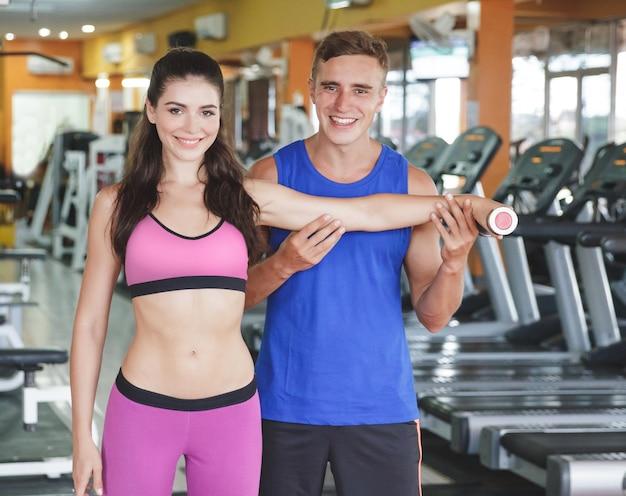 Молодая спортивная женщина тренируется со своим инструктором в тренажерном зале