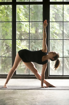 Young sporty woman in extended triangle pose, studio background