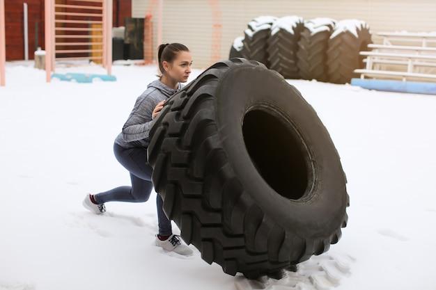 야외에서 무거운 타이어를 내리고 젊은 스포티 한 여자