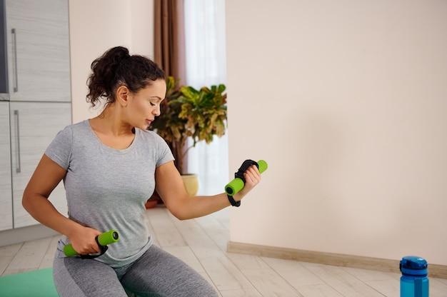 ダンベルで上腕二頭筋のエクササイズをすることに焦点を当てた若いスポーティな女性。自宅で上腕二頭筋のトレーニング