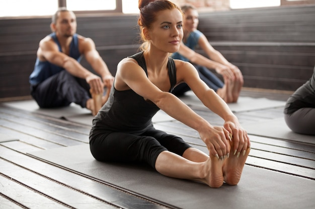 Young sporty woman and a group people in paschimottanasana pose
