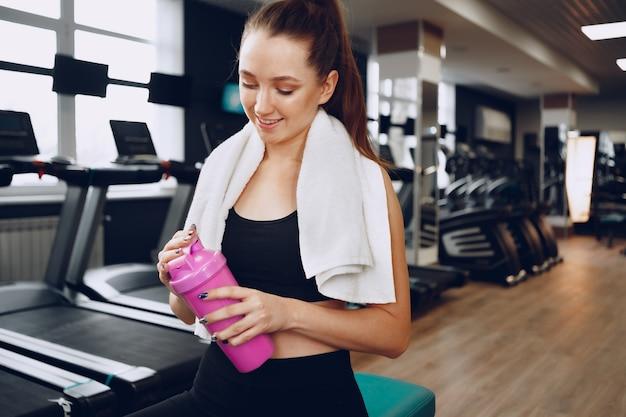 Молодая спортивная женщина с напитком в тренажерном зале после тренировки