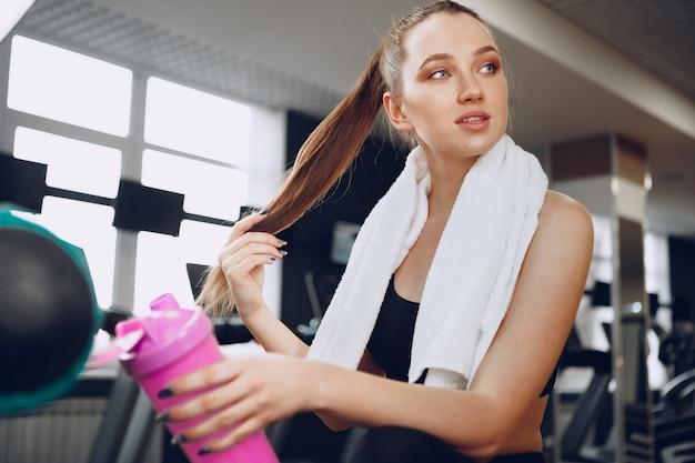 トレーニングの後、ジムでドリンクを持っている若いスポーティな女性