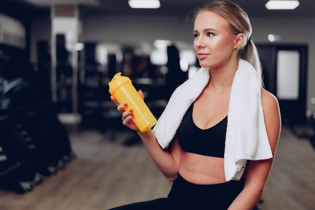 Young sporty woman having a drink in a gym after workout