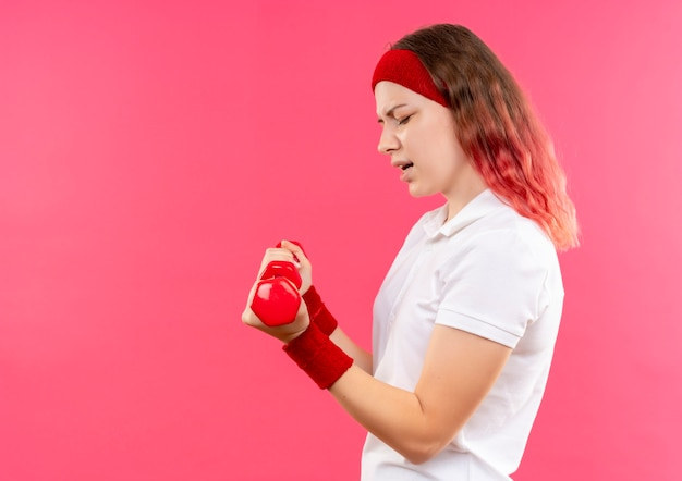 Giovane donna sportiva in fascia facendo esercizi con manubri cercando tesa in piedi sopra il muro rosa