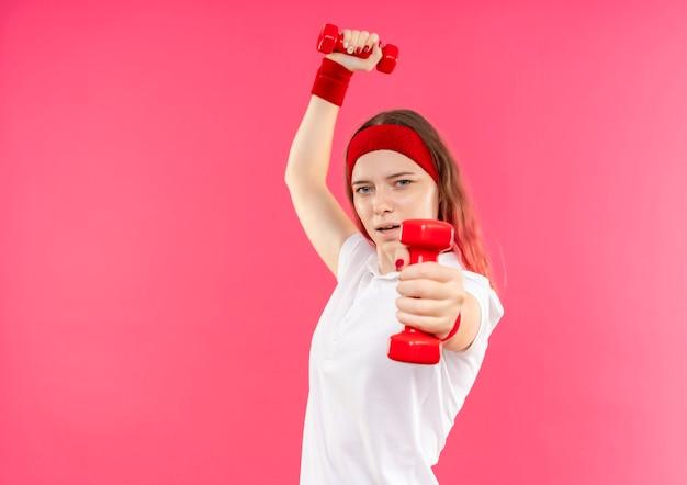 Giovane donna sportiva in fascia facendo esercizi con manubri con espressione seria fiduciosa in piedi sopra il muro rosa