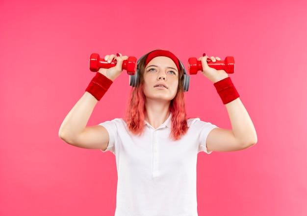Giovane donna sportiva in fascia che tiene due manubri facendo esercizi in piedi sopra la parete rosa