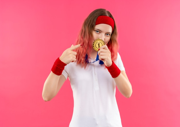 Young sporty woman in headband showing gold medal pointing with finger to it looking confident standing over pink wall