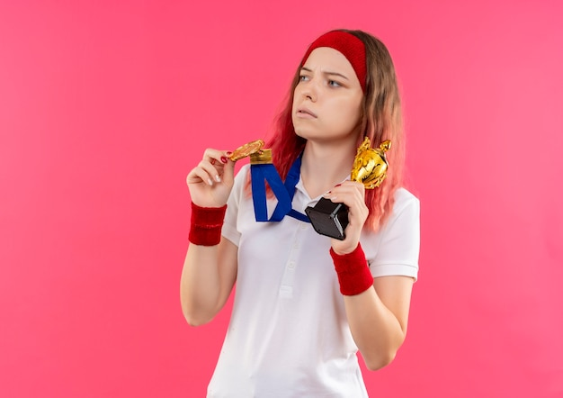 Young sporty woman in headband with gold medal around her neck holding trophy looking aside with serious expression standing over pink wall