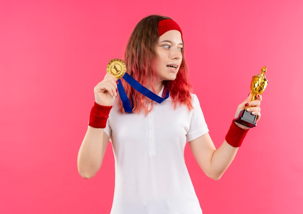 Young sporty woman in headband with gold medal around her neck holding trophy looking at it happy and exited standing over pink wall