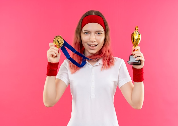 Young sporty woman in headband with gold medal around her neck holding trophy with smilie on face standing over pink wall