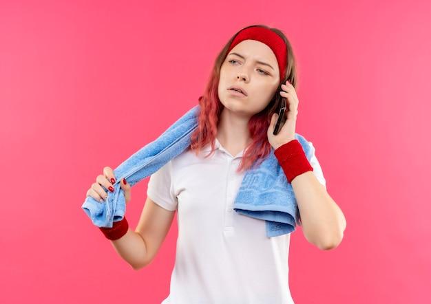 Giovane donna sportiva in fascia con asciugamano sulla spalla che guarda da parte con faccia seria mentre parla al telefono cellulare in piedi sopra la parete rosa