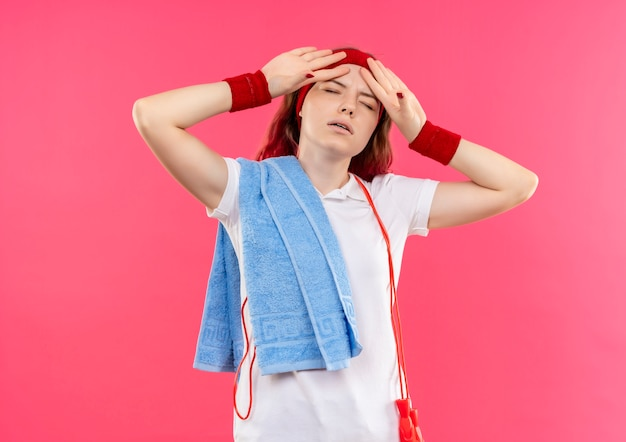 Young sporty woman in headband with towel on shoulder looking tired and exhausted standing over pink wall