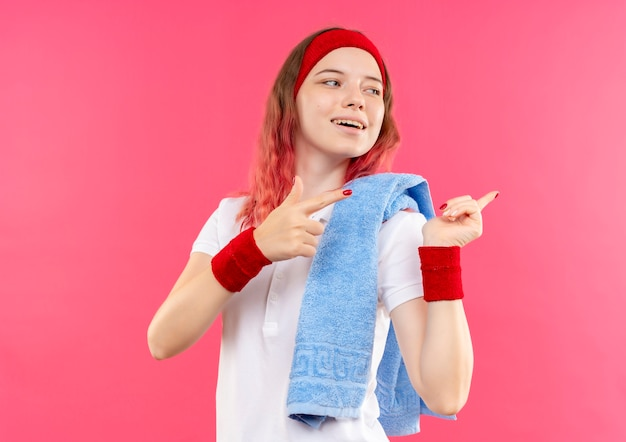 Young sporty woman in headband with towel on shoulder pointing with fingers to the side smiling with happy face standing over pink wall