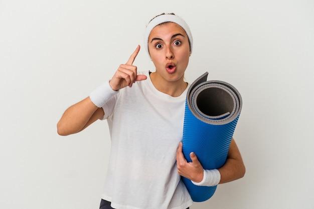 Молодая спортивная женщина, держащая циновку, изолированную на белом фоне, имея идею, концепцию вдохновения.