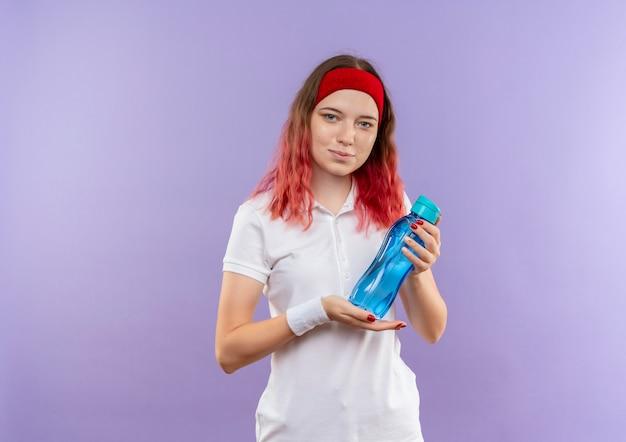 紫色の壁の上に立っている自信を持って笑顔で水のボトルを保持している若いスポーティな女性