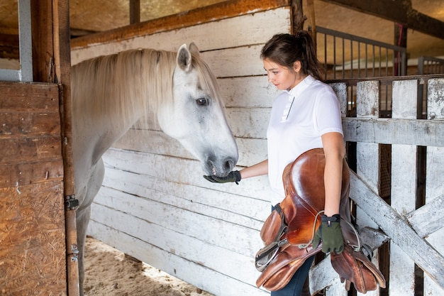 Young sporty woman holding brown leather saddle while feeding white purebred racehorse inside stable before race