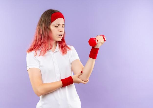 Giovane donna sportiva che tiene un manubrio facendo esercizi guardando il gomito sensazione di dolore in piedi sopra la parete viola
