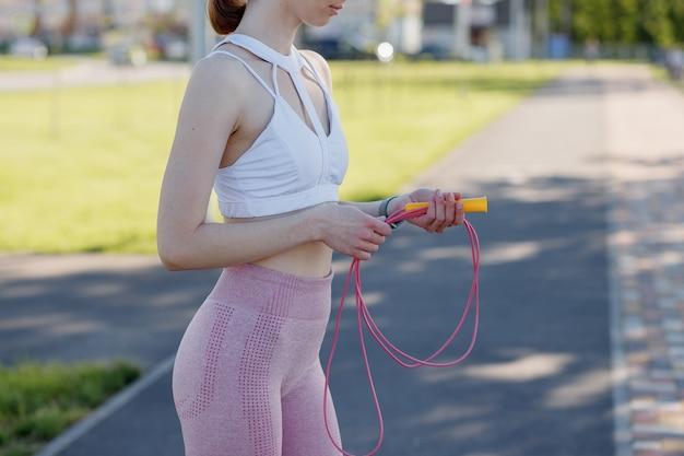 屋外でスポーツロープを保持している若いスポーティな女性