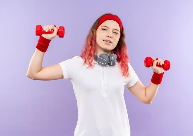 Giovane donna sportiva che tiene due manubri facendo esercizi con un sorriso sicuro in piedi sopra la parete viola
