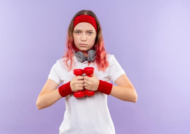 Giovane donna sportiva che tiene due manubri facendo esercizi con la faccia seria in piedi sopra la parete viola