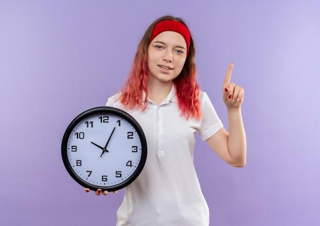 Orologio da parete della tenuta della giovane donna sportiva che sembra puntare fiducioso con il dito in piedi sopra la parete viola
