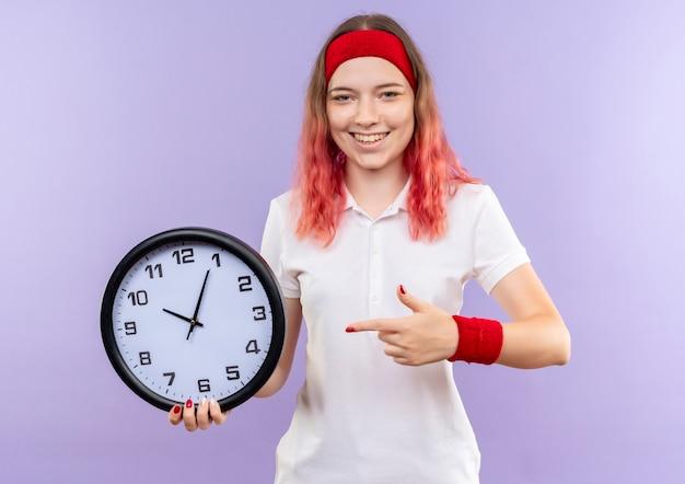 Orologio da parete della tenuta della giovane donna sportiva che indica con il dito che sorride allegramente in piedi sopra la parete viola