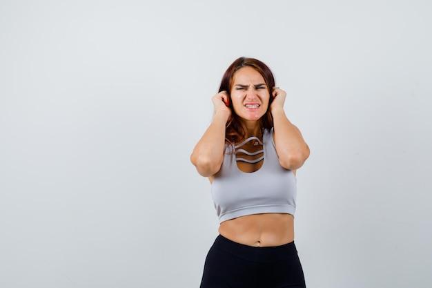 彼女の耳を覆う灰色のトップの若いスポーティな女性