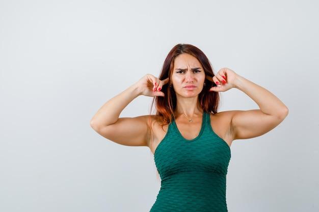 Молодая спортивная женщина в зеленом облегающем платье закрывает уши