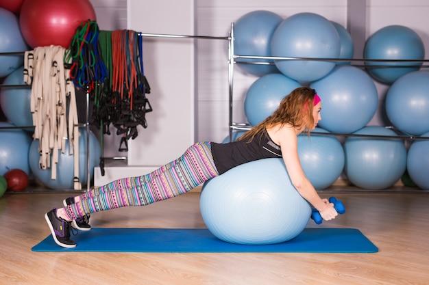 青いボールでフィットネス運動をしているジムで若いスポーティな女性