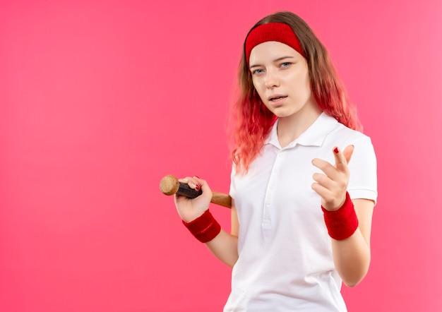 ピンクの壁の上に立っているカメラに指で自信を持って指している野球のバットを保持しているヘッドバンドの若いスポーティな女性