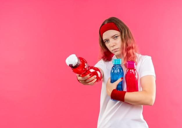 ピンクの壁の上に立っているボトルの1つを提供する水のボトルを保持しているヘッドバンドの若いスポーティな女性