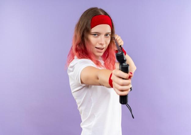 보라색 벽 위에 서있는 것을 목표로 건너 뛰는 밧줄을 들고 머리띠에 젊은 스포티 한 여자