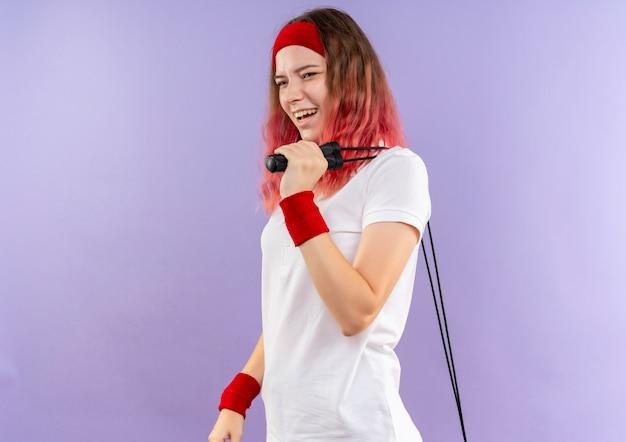 보라색 벽 위에 유쾌하게 서 웃 고 옆으로 찾고 건너 뛰는 밧줄을 들고 머리 띠에 젊은 스포티 한 여자