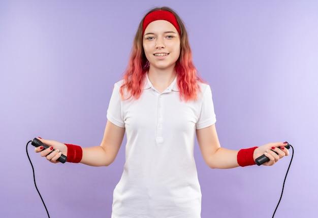 보라색 벽 위에 서있는 훈련을 유쾌하게 웃고있는 줄넘기를 들고 머리띠에 젊은 스포티 한 여자