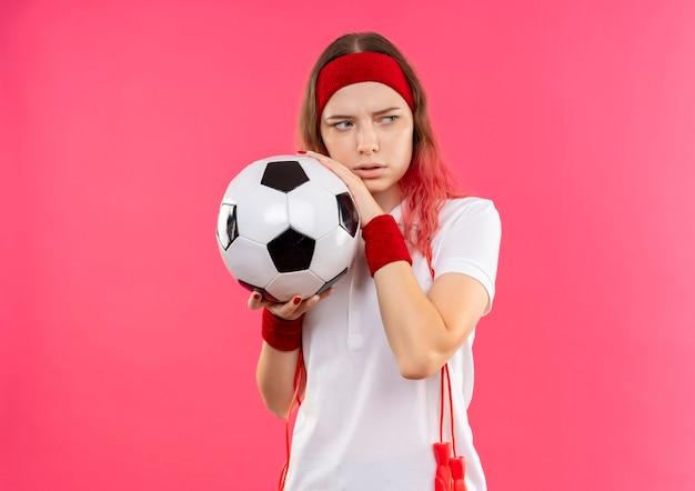 분홍색 벽 위에 서있는 두려움 식으로 제쳐두고 찾고 축구 공을 들고 머리띠에 젊은 스포티 한 여자