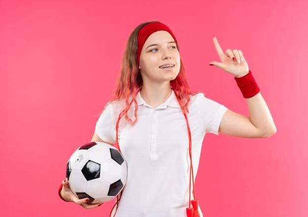 Молодая спортивная женщина в повязке на голову, держащая футбольный мяч, указывая вверх указательным пальцем, выглядит уверенно, стоя над розовой стеной