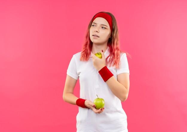 분홍색 벽 위에 서있는 잠겨있는 표정으로 옆으로 찾고 두 개의 사과를 들고 머리띠에 젊은 스포티 한 여자