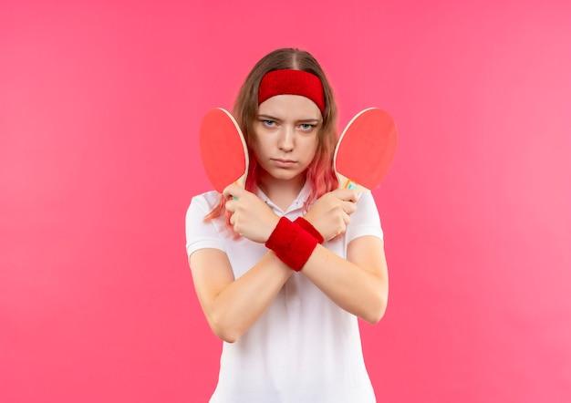 분홍색 벽 위에 서 심각한 얼굴로 손을 건너 테이블 탁구에 대한 두 개의 라켓을 들고 머리띠에 젊은 스포티 한 여자