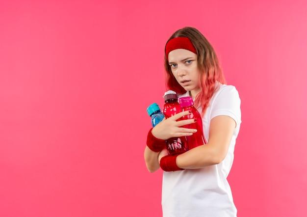 Молодая спортивная женщина в ободке обнимает бутылки с водой с выражением страха над розовой стеной