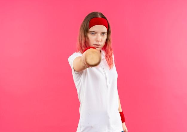 ピンクの壁の上に立って自信を持って見えるコウモリとカメラを指しているヘッドバンドの若いスポーティな女性