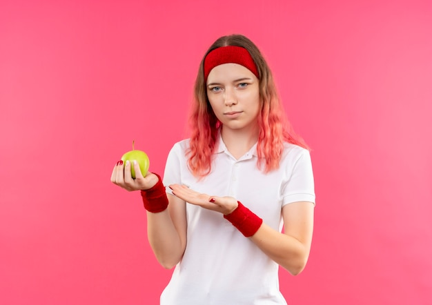 ピンクの壁の上に立って自信を持って見える彼女の手の腕と青リンゴを提示するヘッドバンドの若いスポーティな女性