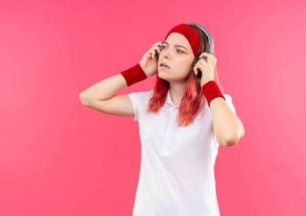 ピンクの壁の上に立って脇を見ながら音楽を聴いているヘッドフォンでヘッドバンドの若いスポーティな女性