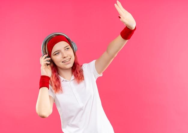 ピンクの壁の上に立っている手で幸せで前向きに手を振って脇を見ているヘッドフォンでヘッドバンドの若いスポーティな女性