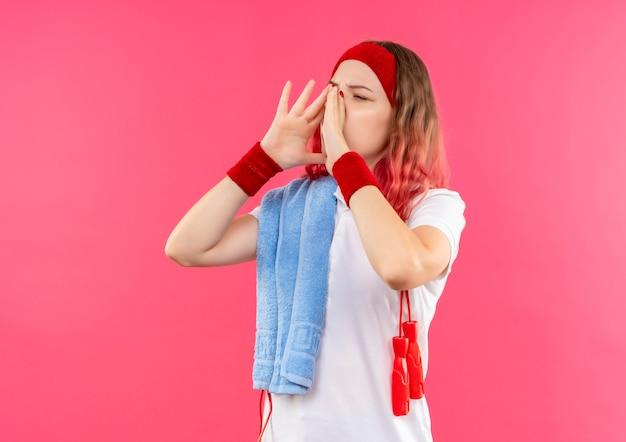 ピンクの壁の上に立っている口の近くの手のひらで誰かを呼び出す肩にタオルでヘッドバンドの若いスポーティな女性