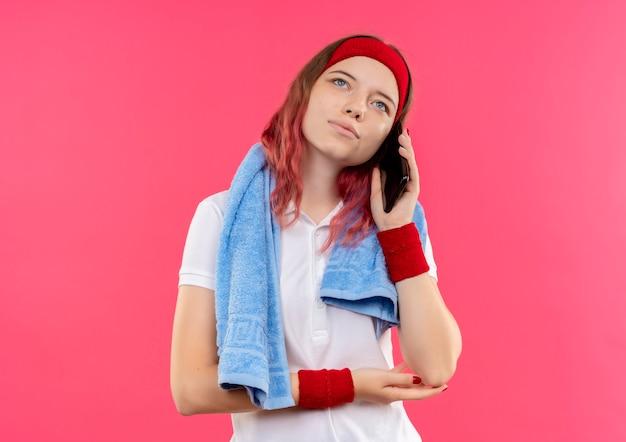 어깨에 수건으로 머리띠에 젊은 스포티 한 여자는 분홍색 벽 위에 서있는 휴대 전화로 이야기하는 동안 웃고 꿈꾸는 표정으로 옆으로 찾고